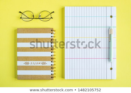 Eyeglasses, closed notebook with spiral binder, pen and lined paper Stock photo © pressmaster