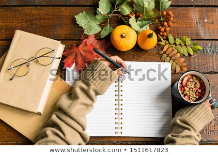 Female student hands with pen and hot drink making notes in copybook Stock photo © pressmaster