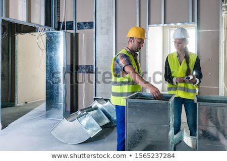 Construction workers inspecting parts of ventilation shafts to be installed Stock photo © Kzenon