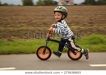 Little boy on a balance bike. Caught in motion, on a driveway. Preschool child's first day on the bi Stock photo © galitskaya