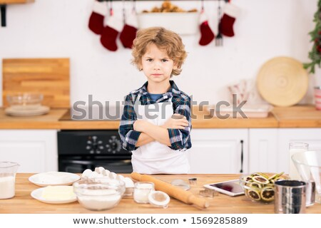 Discontent little boy crossing arms on chest while standing by kitchen table Stock photo © pressmaster