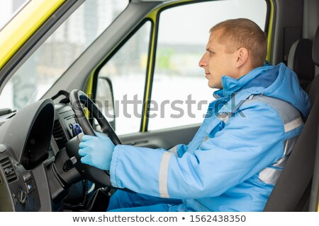 Young driver sitting by steer in ambulance car while waiting for paramedics Stock photo © pressmaster