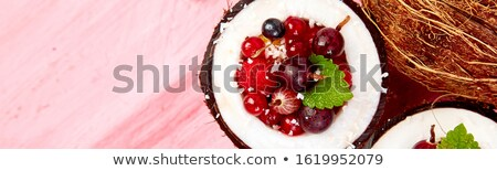 Banner with Fruit salad agrus, gooseberry, rasbberry in coconut shell bowl on a pink table backgroun Stock photo © Illia