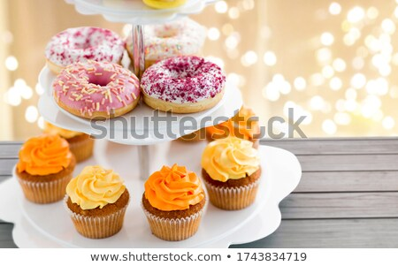 glazed donuts, cupcakes with frosting on stand Stock photo © dolgachov