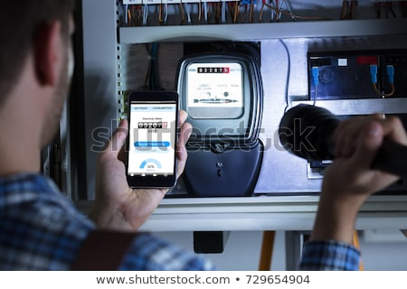 Man's Hand Holding Mobile Phone Showing Electric Meter Reading Stock photo © AndreyPopov