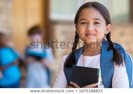 Portrait of a smiling schoolgirl carrying backpack standing Stock photo © deandrobot