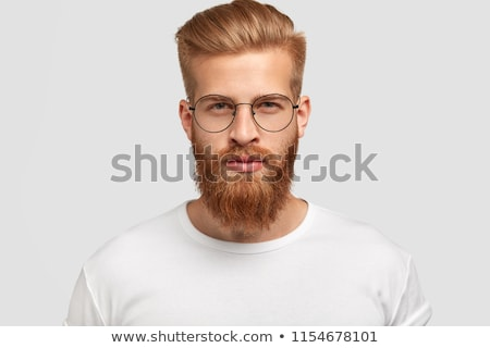 Handsome bearded man with serious expression wears spectacles and glasses, dressed in denim fashiona Stock photo © vkstudio