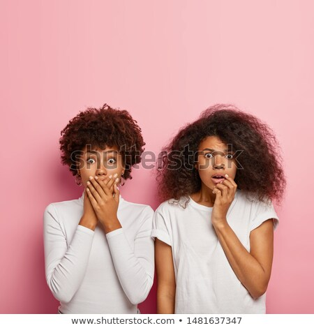Image of two scared girls expressing fright and covering their m Stock photo © deandrobot