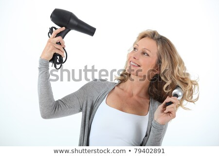 Long haired woman using a hairdryer and large round brush Stock photo © photography33
