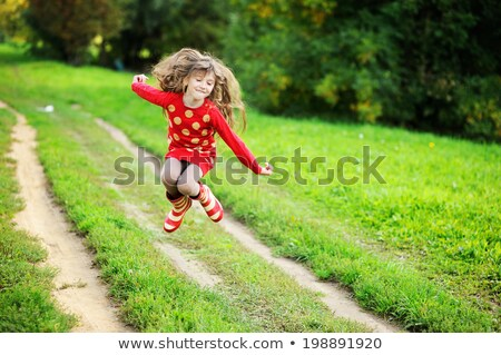 Little girl in green sweater jumping for joy stock photo © jarenwicklund