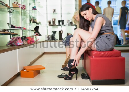 Woman is trying shoes sitting down in a boutique Stock photo © wavebreak_media