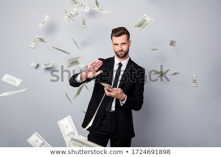 Stock photo: Businessman working on flying money in the air