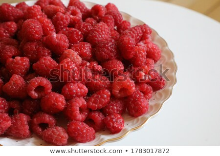 Stock photo: Big Pile of Fresh Raspberries in the Bowl on Green Background