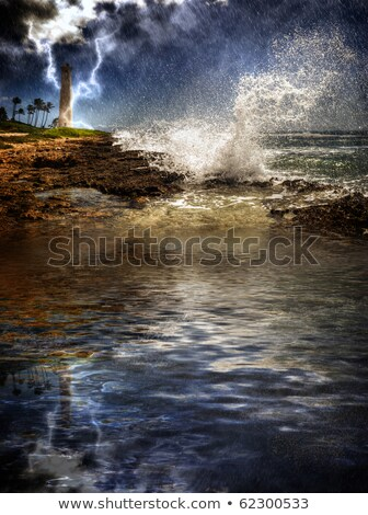 lighthouse along rocky shore with storm clouds in distance stock photo © jameswheeler