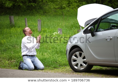 funny driver praying a broken car by the road stock photo © vladacanon
