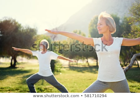 woman doing yoga exercises on the green grass stock photo © deandrobot