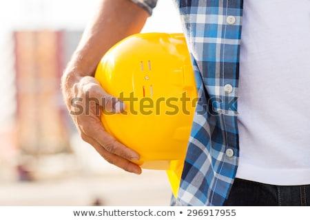 Közelkép építész kéz tart munkavédelmi sisak kint Stock fotó © dolgachov