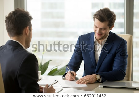 smiling businessman signing papers in office Stock photo © dolgachov