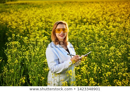 Female agronomist in field of blooming rapeseed Stock photo © stevanovicigor