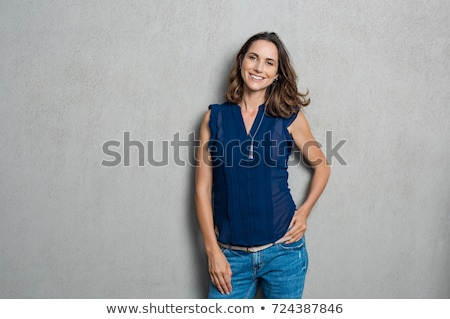 Smiling casual woman leaning on the wall Stock photo © deandrobot