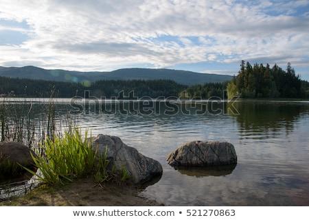 Montanha lago rochas primeiro plano pôr do sol acima Foto stock © Kayco
