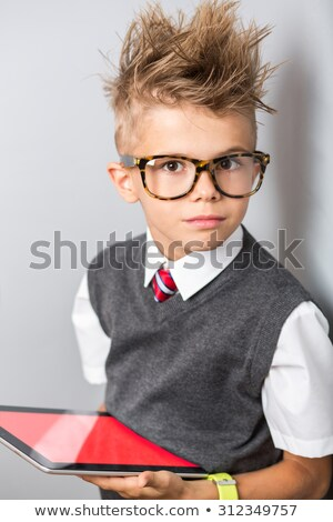 serious little boy in glasses using tablet stock photo © deandrobot