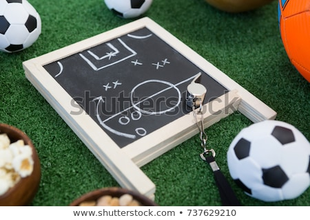 Chalk board, snacks and football on artificial grass Stock photo © wavebreak_media