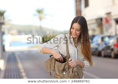 Young woman searching in handbag Stock photo © IS2