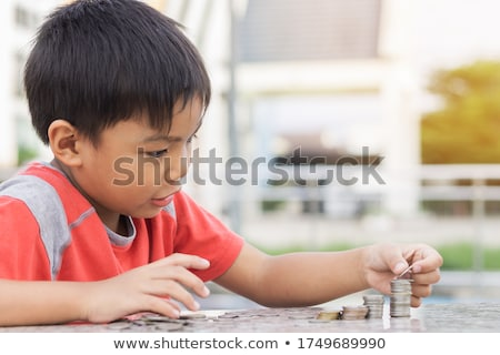 boy counting money at table stock photo © is2