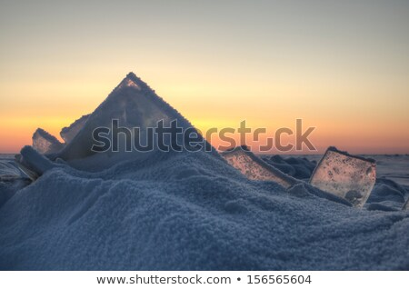 Snowing at a frozen lake with snowflakes gleaming in sunlight Stock photo © Mps197
