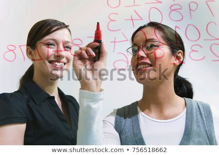 two women work on figures on glass wall stock photo © is2