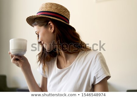 Cropped image of woman in straw hat using smartphone Stock photo © deandrobot