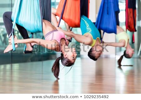 Fitt fiatal nő gyakorol légi jóga csoport Stock fotó © Kzenon