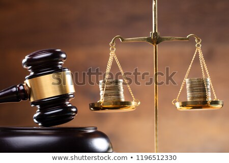 close up of gavel and stacked coins on justice scale stock photo © andreypopov