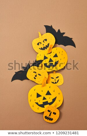 Smiling scary pumpkins and bat handcraft of paper on a brown background with space for text. Hallowe Stock photo © artjazz