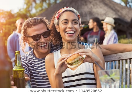 Young friends party outdoors in park having fun eat burgers. Stock photo © deandrobot