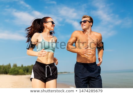 Sportsman outdoors at the beach listening music with earphones drinking water. Stock photo © deandrobot