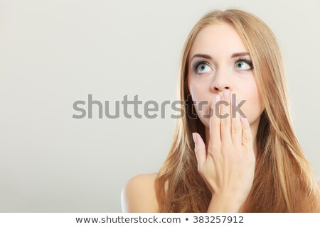 Worried woman with her hand over mouth Stock photo © Kzenon