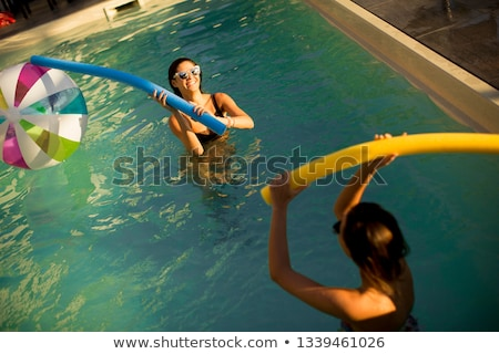 Young women having fun  with swimming pool noodles Stock photo © boggy