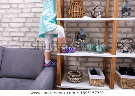 Girl Trying To Climb On Shelf Stock photo © AndreyPopov