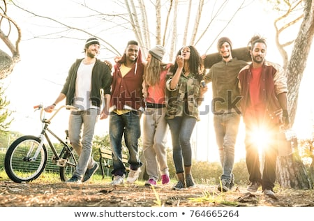 Multiracial young people walking in the autumn park and having f Stock photo © boggy