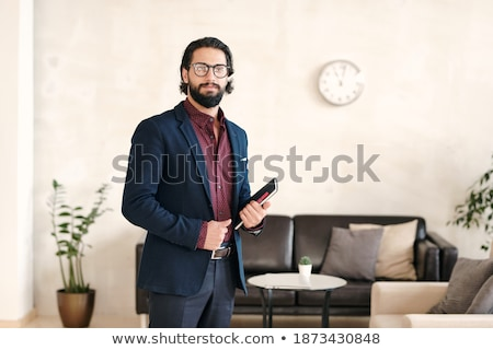 Young African businessman with mobile phone standing by table in front of camera Stock photo © pressmaster