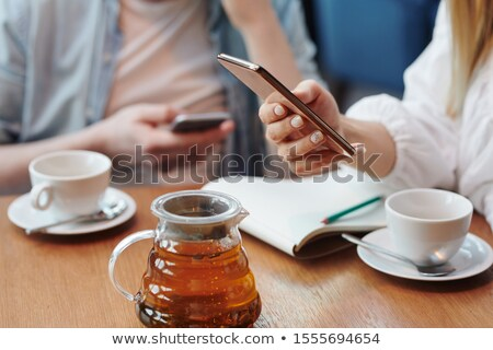 Hand of female millennial scrolling in smartphone over table while having tea Stock photo © pressmaster