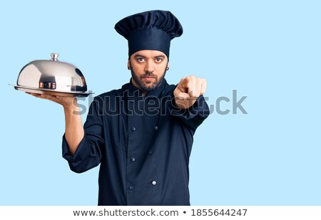 Successful young bearded chef in uniform looking at you with toothy smile Stock photo © pressmaster