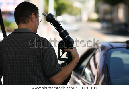 man pointing fuel nozzle at his head stock photo © iodrakon