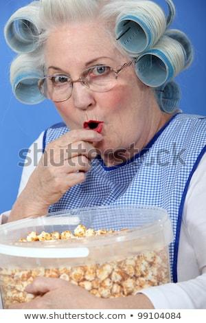 Granny eating caramel popcorn Stock photo © photography33