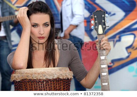 musician leaning on a drum and holding a guitar stock photo © photography33