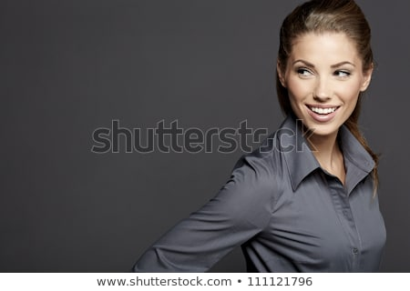 Pretty young brunette woman smiling against gray background with stock photo © HASLOO