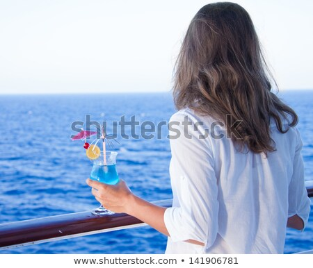 Stock photo: pretty girl with a cold drink, admiring the sea views
