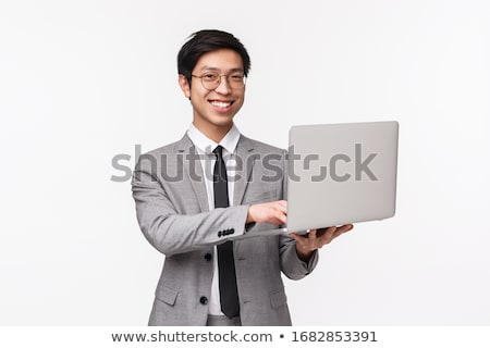 confident businessman using laptop on gray background stock photo © deandrobot